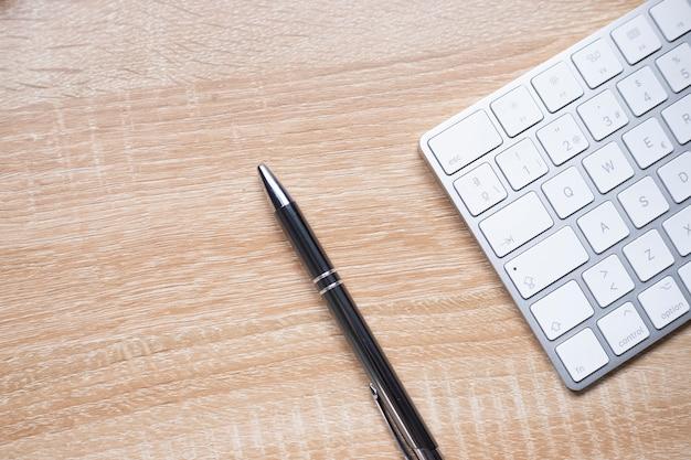 Table de bureau en bois avec clavier et stylo, vue de dessus avec espace copie