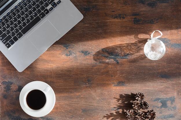 Table de bureau en bois foncé avec ordinateur portable et tasse à café. vue de dessus et mise à plat avec espace de copie, fond d'hiver