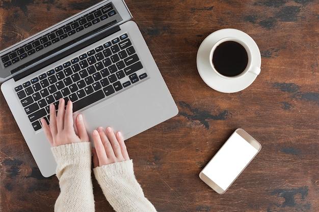 Table de bureau en bois foncé avec ordinateur portable, téléphone portable. vue de dessus et mise à plat avec espace de copie, fond d'hiver