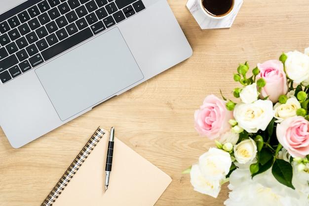 Table de bureau en bois moderne avec ordinateur portable, bouquet de fleurs, tasse de café, bloc-notes en papier, stylo.