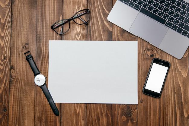 Table de bureau en bois avec ordinateur portable, téléphone, papier blanc clair et fond de fournitures de bureau.