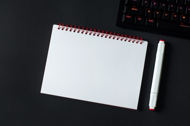 Table de bureau avec cahier vierge et clavier.