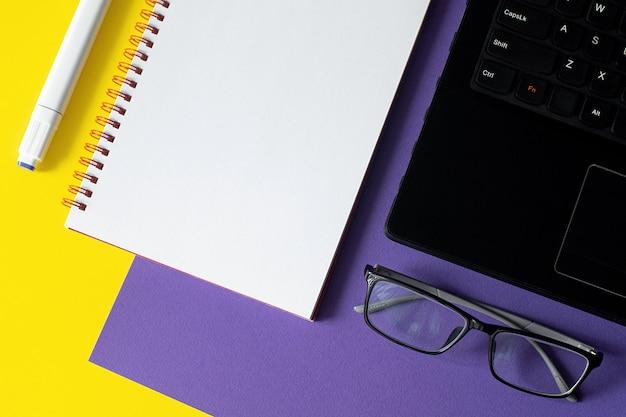 Table de bureau avec cahier vierge et ordinateur portable.