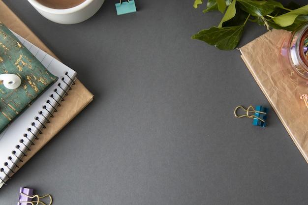 Table de bureau avec cahiers, fournitures de bureau, plante verte et tasse à café.