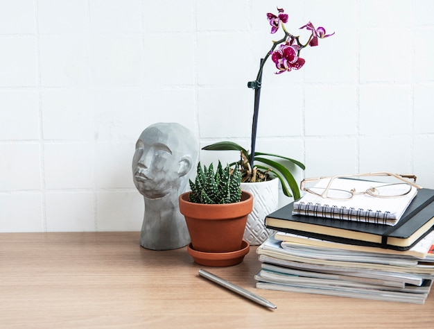 Table de bureau avec cahiers, fournitures et plantes d'intérieur