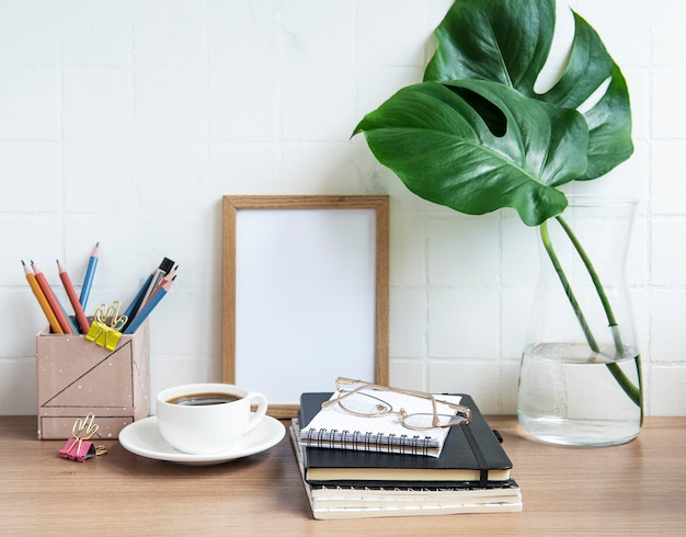 Table de bureau avec cahiers, fournitures et tasse à café.