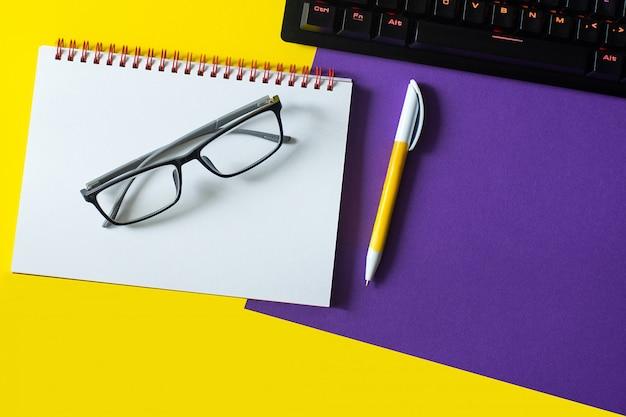 Table de bureau avec carnet vierge et clavier et lunettes.