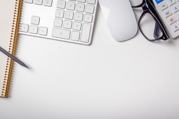 Table de bureau avec clavier d'ordinateur, fournitures, calculatrice, stylo, lunettes