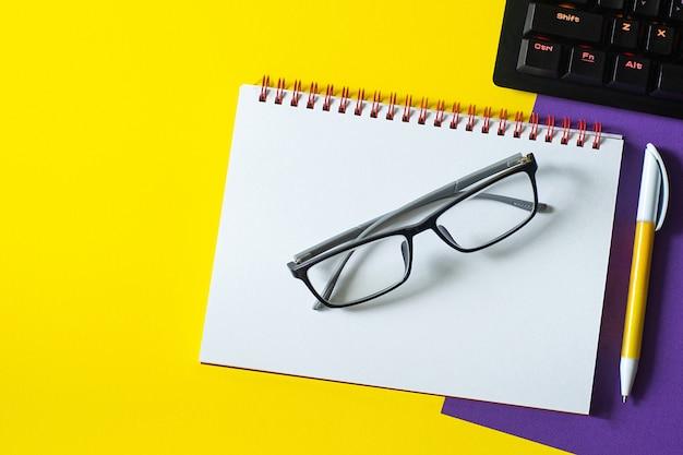 Table de bureau avec clavier vierge et lunettes