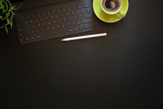 Table de bureau en cuir foncé avec café, ordinateur et fournitures de bureau.