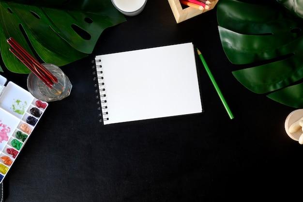 Table de bureau en cuir avec fournitures créatives, aquarelle et fleur.