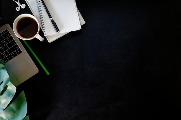 Table de bureau en cuir avec ordinateur portable, fournitures et tasse à café.