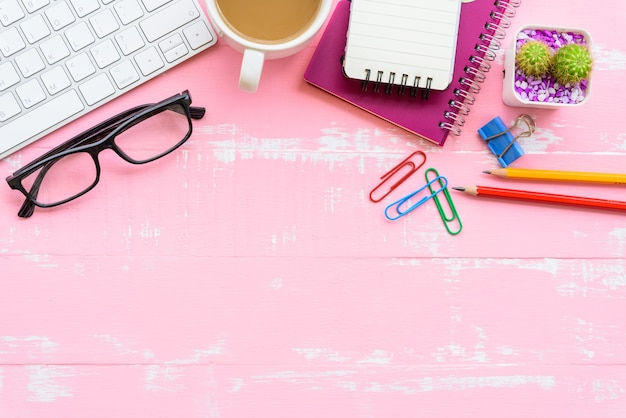 Table de bureau avec espace de travail et accessoires de bureau sur un fond en bois rose.