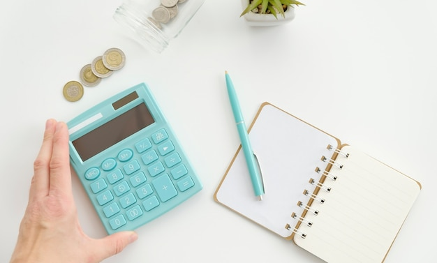 Table de bureau avec fleur, bloc-notes vierge et main.
