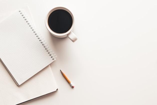 Table de bureau avec fournitures, tasse à café et fleur. vue de dessus avec espace copie