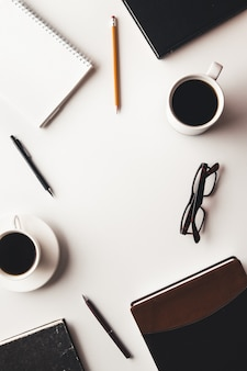Table de bureau avec fournitures, tasse à café et fleur. vue de dessus