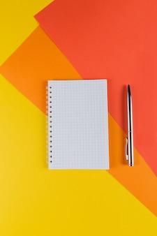 Table de bureau jaune et orange avec cahier vierge et autres fournitures de bureau. vue de dessus avec espace copie, mise à plat.