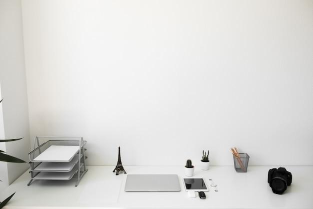 Table de bureau sur laquelle ordinateur portable, café, tablette, appareil photo et autres articles