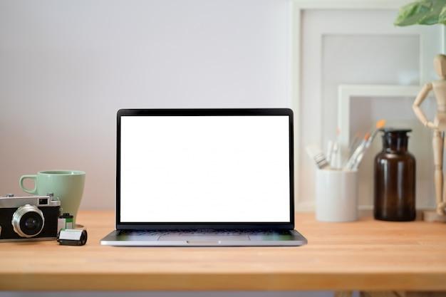 Table de bureau loft en bois avec ordinateur portable, affiche, appareil photo vintage et fournitures.