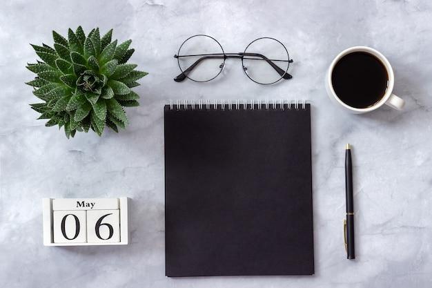 Table de bureau ou de maison, calendrier le 6 mai. bloc-notes, tasse de café, succulent, verres sur marbre
