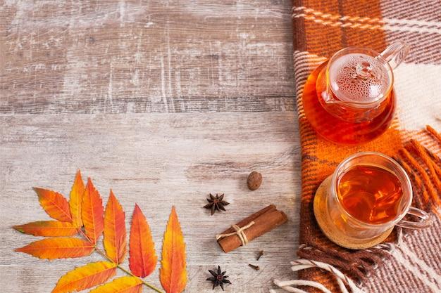 Table de bureau à la maison avec plaid orange à carreaux et feuilles d'automne de tasse de thé