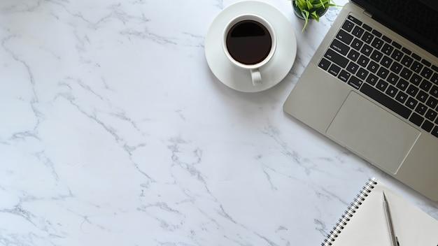 Table de bureau en marbre avec ordinateur portable, stylo, ordinateur portable et café avec plante, espace de travail professionnel plat.