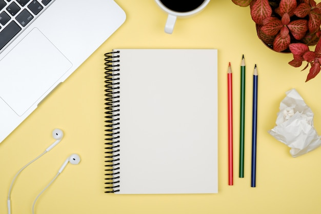 Table de bureau moderne avec ordinateur portable et page de cahier vierge