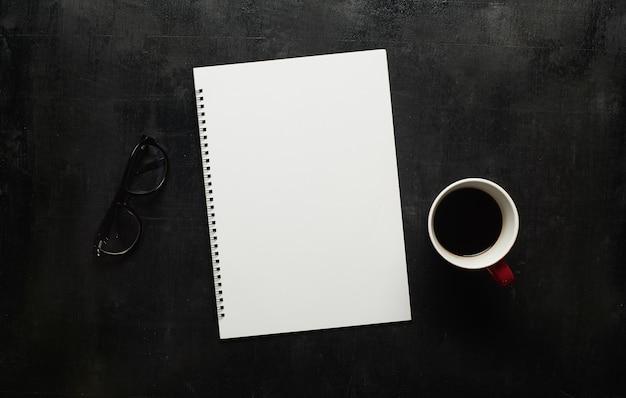 Table de bureau noire en bois avec cahier, lunettes et tasse de café