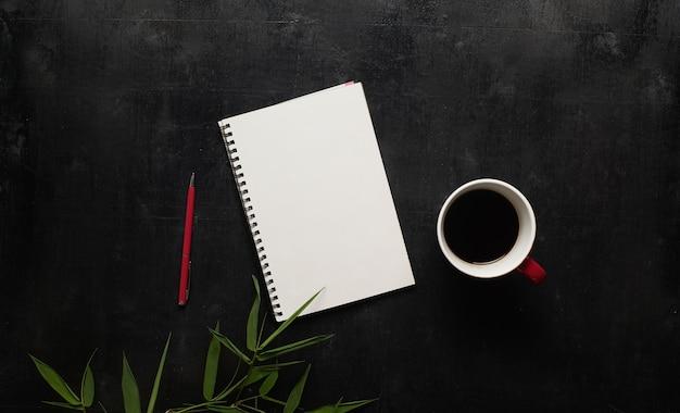 Table de bureau noire en bois avec cahier, stylo et tasse de café