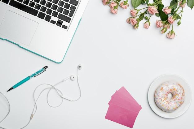 Table de bureau avec ordinateur, fournitures, fleurs