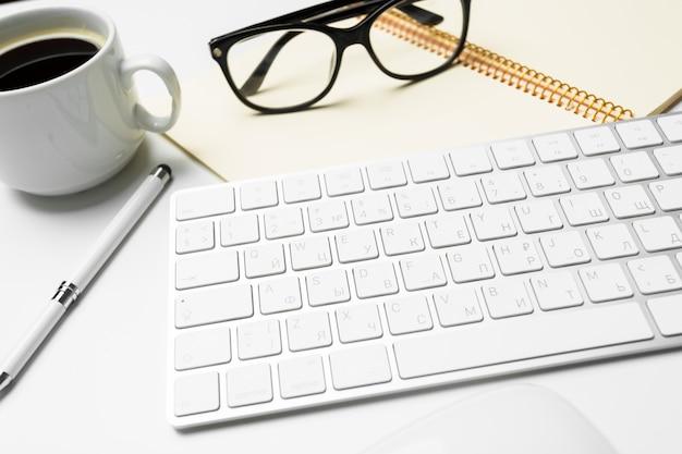Table de bureau avec ordinateur, fournitures, tasse à café