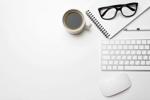 Table de bureau avec ordinateur, fournitures et tasse à café