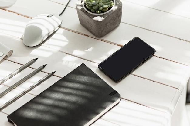 Table de bureau avec ordinateur, fournitures et téléphone
