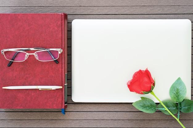 Table de bureau avec ordinateur portable, cahier, rose rouge