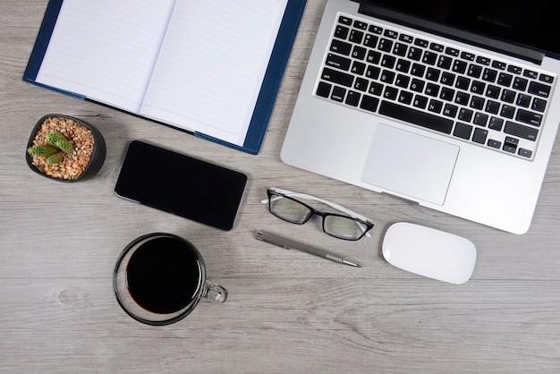 Table de bureau avec ordinateur portable, ordinateur portable, tablette numérique et smartphone sur bois