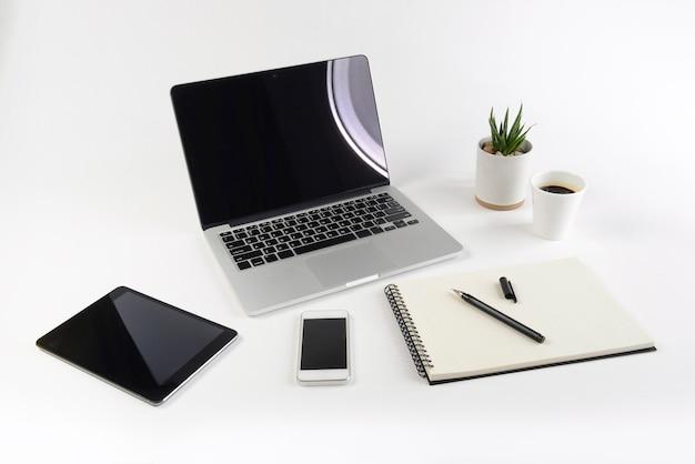 Table de bureau avec ordinateur portable, ordinateur portable, tablette numérique et smartphone sur fond blanc.