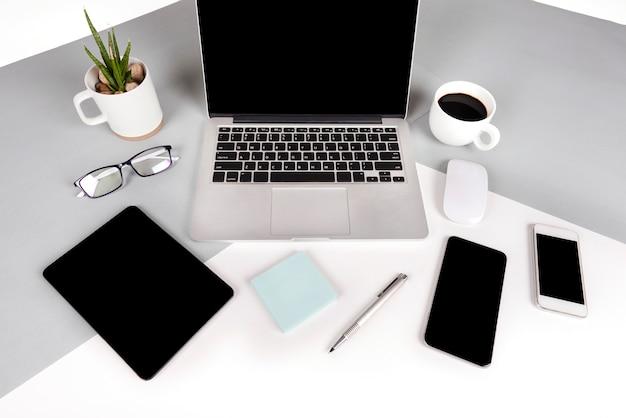 Table de bureau avec ordinateur portable, ordinateur portable, tablette numérique et téléphone portable sur deux tons b