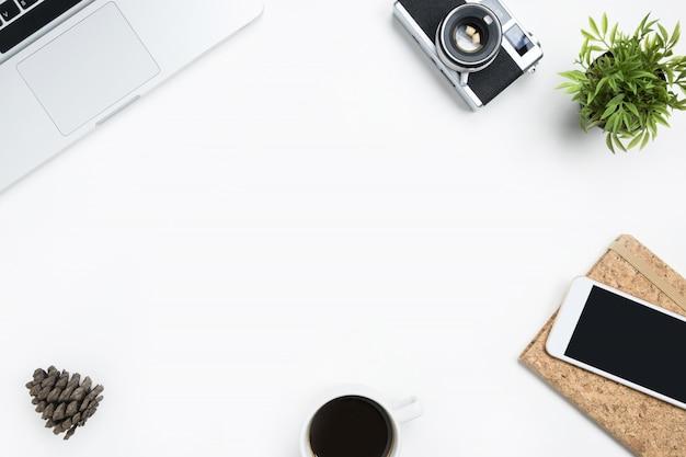 Table de bureau de photographe blanche avec appareil photo argentique, ordinateur portable et fournitures.