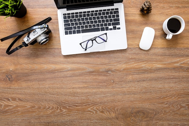 Table de bureau de photographe en bois avec appareil photo argentique, ordinateur portable, tasse de café et fournitures. vue de dessus avec espace de copie, pose à plat.