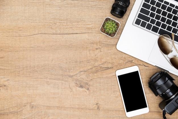 Table de bureau de photographe en bois avec appareil photo, objectif de caméra, ordinateur portable, smartphone et accessoires. vue de dessus avec espace de copie, pose à plat.