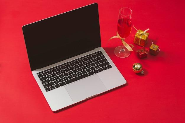 Table de bureau à plat, vue de dessus. espace de travail avec ordinateur portable et décorations de noël sur surface rouge