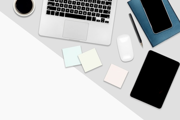 Table de bureau plate avec ordinateur portable, tablette numérique, téléphone portable et accessoires.