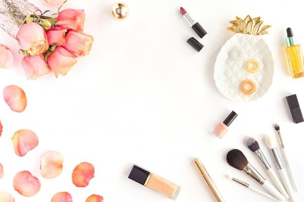 Table de bureau rose avec des fleurs, maquillage, pinceau et cosmétiques. accessoires femme, concept de surface