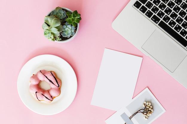 Table de bureau rose moderne avec ordinateur portable, fleur succulente, beignet et papier vierge pour texte.