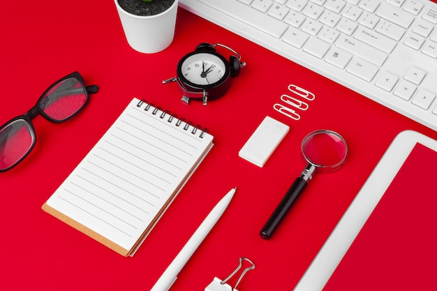 Table de bureau rouge avec bloc-notes, clavier et fournitures vierges. vue de dessus avec espace de copie. lay plat.