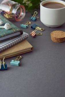Table de bureau de style minimaliste avec des cahiers, des fournitures de bureau et une tasse à café.