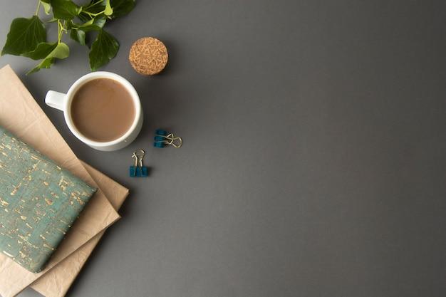Table de bureau stylisée avec cahier vierge, fournitures de bureau et tasse à café. espace de copie.