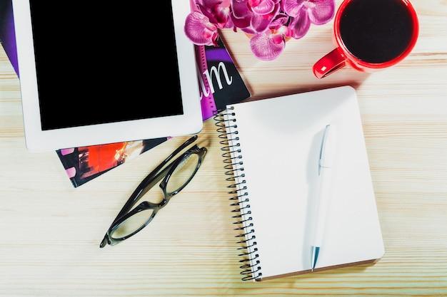 Table de bureau avec tablette numérique, feuille de papier vide pour smartphone et tasse de café.