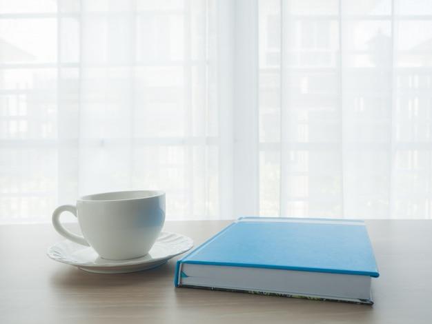 Table de bureau avec tasse à café blanche et papier de cahier bleu sur la fenêtre de rideau blanc backgro