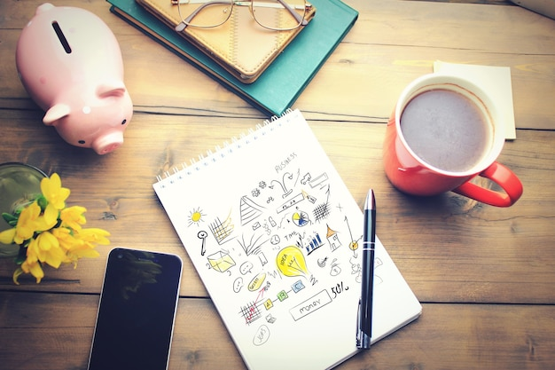 Table de bureau avec une tasse à café, un plan sur bloc-notes